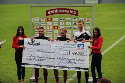 Die Fußballprofis Lukas Podolski (2.v.l.) und Per Mertesacker (2.v.r.) sowie Markus Krampe (M.), Geschäftsführer Pro-Event, freuten sich über 100.000 Euro, die bei dem Benefizspiel für die Lukas Podolski Stiftung und die Per Mertesacker Stiftung zusammenkamen.