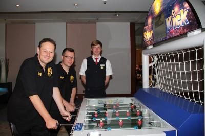 """Lukas Haufs-Brunsberg (hinten) stellte den Gästen die innovativen Geräte der Gauselmann Gruppe vor. Hier treten Jörg Lippold (vorne) und Jürgen Godlewski gegen den Kickerroboter """"Star Kick"""" an."""