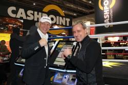 Prominenter Besuch auf dem Cashpoint Messestand auf der IMA 2014: Axel Schulz und Pierre Littbarski vor dem neuen Merkur Bet Book.