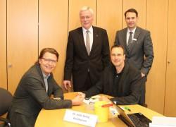 Dr. Georg Backhausen (sitzend rechts) untersucht Armin Gauselmann (sitzend links) beim Auftakt der Schlaganfall-Info-Tour. Georg Droste (stehend links) und Marc Schäuble (stehend rechts), Sparkasse Minden-Lübbecke, begrüßen die Gäste zum Auftakt der Tour.