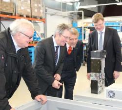 Paul Gauselmann (2.v.r.) und Hans Martin Grube (1.v.r.), Werksleiter adp, erklären Achim Post (2.v.l.), SPD-Bundestagsabgeordneter des Mühlenkreises, und Arnold Oevermann (1.v.l.), SPD Fraktionsvorsitzender aus Lübbecke, die Merkur Dispenser-Produktion im adp-Werk in Lübbecke.