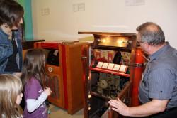 """Josef Herb aus der Museumswerkstatt erläuterte den Besuchern die Jukeboxen-Technik der 1950er Jahre. Für die Kinder unter den Gästen waren aber nicht nur die historischen Jukeboxen, sondern ebenso die Schallplatten von Interesse: solche """"komischen Scheiben""""  waren ihnen gänzlich unbekannt."""