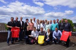 Spitzensport mit Spitzenpartnern: Die Vertreter der SG Coesfeld 06 und die Sponsoren des Sparkassen Beach Premium Cups präsentieren sich als starkes Team auf der Dachterrasse bei der Schmidt Gruppe.