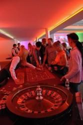 Besucher erhalten eine Spielerklärung am Roulette Tisch.