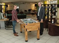 Anton Schick, Real Life e.V., (l.) und Mario Hoffmeister, Gauselmann Gruppe, (r.) sind davon überzeugt, dass sich der neue Kicker im Espelkamper Jugend-Café großer Beliebtheit erfreuen wird.