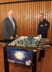 Uwe Nelle-Cornelsen, Leiter der Justizvollzugsanstalt Bielefeld-Brackwede, (l.) und Michael Wosch, Justizvollzugshauptsekretär, (r.) an einem der vier Kickertische, die die Gauselmann Gruppe für das JVA-Turnier zur Verfügung gestellt hat.