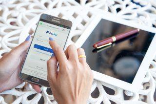 Frau loggt sich auf Smartphone bei PayPal ein