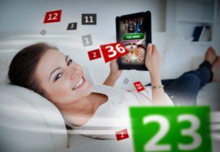 Frau mit Tablet beim Online Casino Spielen auf der Couch