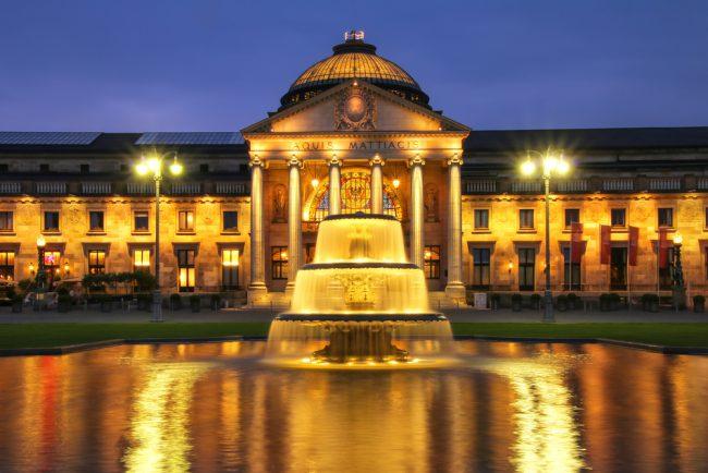 Nächtliche Frontansicht des hell erleuchteten Kurhauses Wiesbaden.