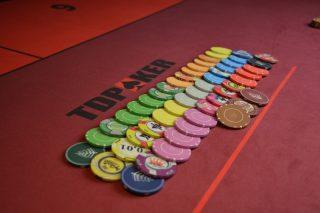 Unterschiedliche Casino-Chips aufgereiht auf einem Poker-Tisch