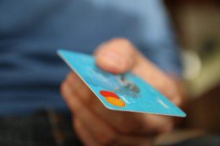 Mann hält eine Kreditkarte in seiner Hand.