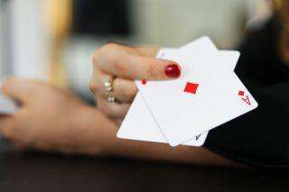Frau hält zwei Spielkarten in die Kamera.