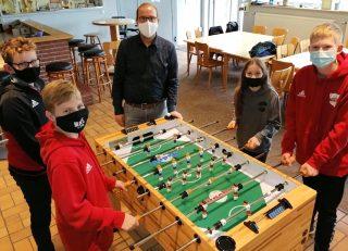 Schuss und Tor: Der 1.Vorsitzende, Daniel Helmerking, und die Kinder haben beim Spielen am neuen Kicker sichtlich Spaß.