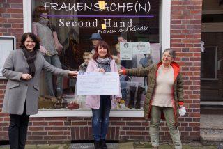 """Die Scheckübergabe fand vor dem Kleidungsgeschäft """"Frauensache"""" in der Dorstener Altstadt statt, der dem Verein """"Frauen helfen Frauen"""" gehört und von Ehrenamtlichen betrieben wird."""