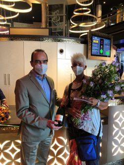 Spielbank-Chef Gerhard Wilhelm begrüßt die erste Besucherin am neuen Standort am Kurfürstendamm persönlich mit einem Blumenstrauß und einer Flasche Champagner. (Foto: Spielbank Berlin)