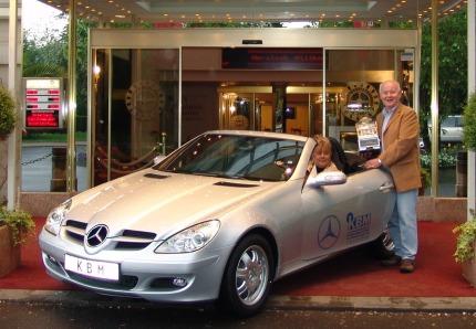 Das glückliche Gewinnerehepaar holt ihren Auto-Jackpotgewinn ab.